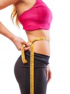 portrait of pretty sporty woman measuring her body